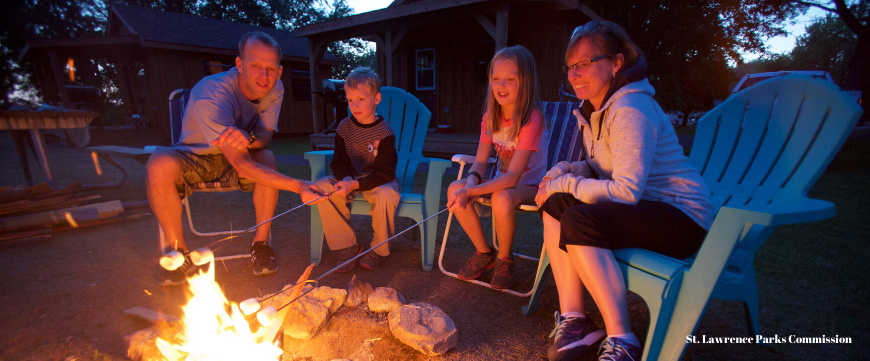 Family of four roasting marshmallows on open fire while camping