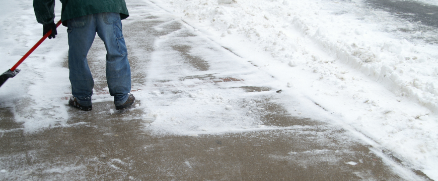 Sidewalk in the winter with man shoveling snow off